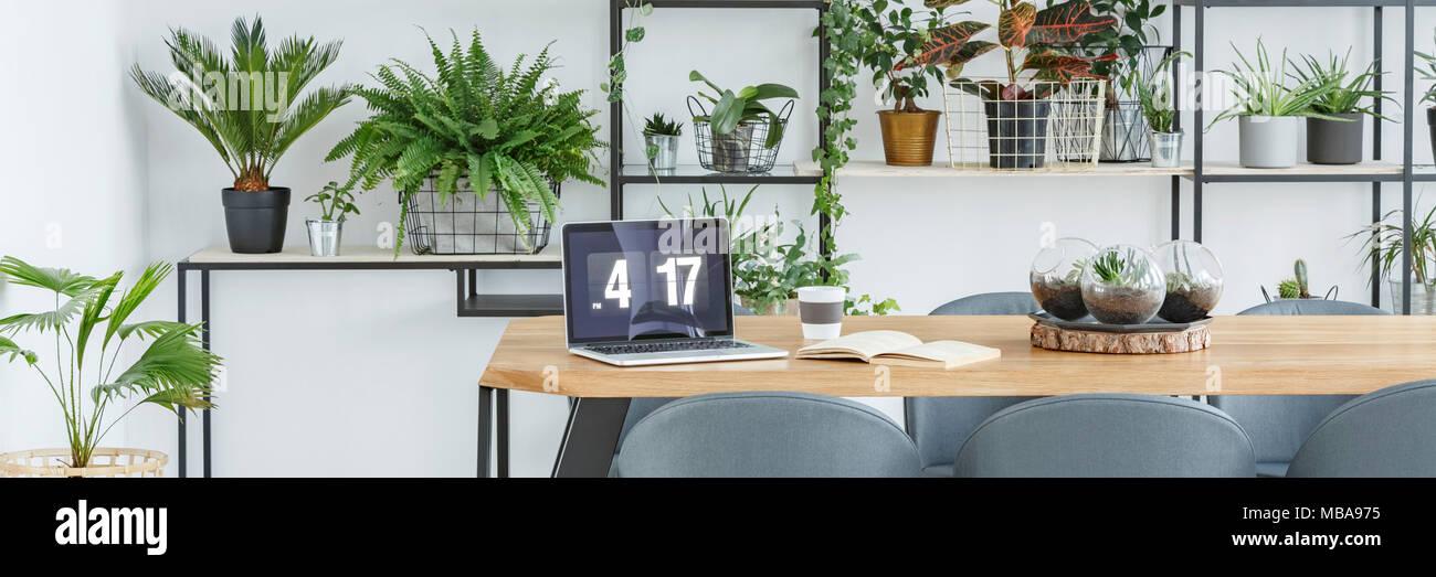 Kaffeetasse, Laptop und geöffnete Buch auf einen hölzernen Tisch in weißer Innenausstattung mit vielen Pflanzen Stockbild