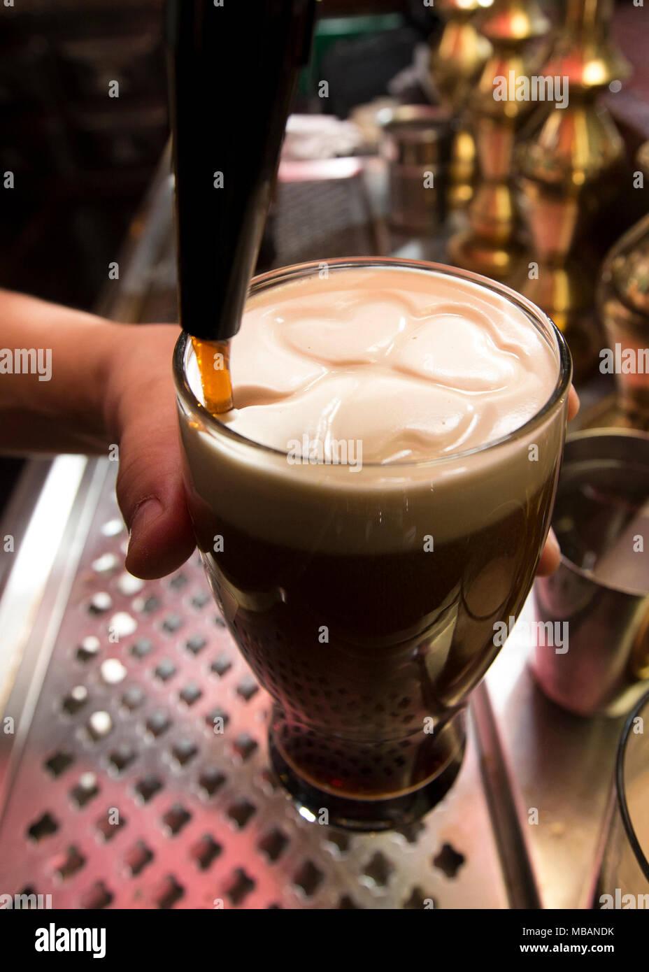 Nahaufnahme von einem Barkeeper Zeichnung ein Kleeblatt in der Bier Schaum mit dem Bier. Er gießt ein dunkel schwarz irisches Bier an der Theke. Stockbild