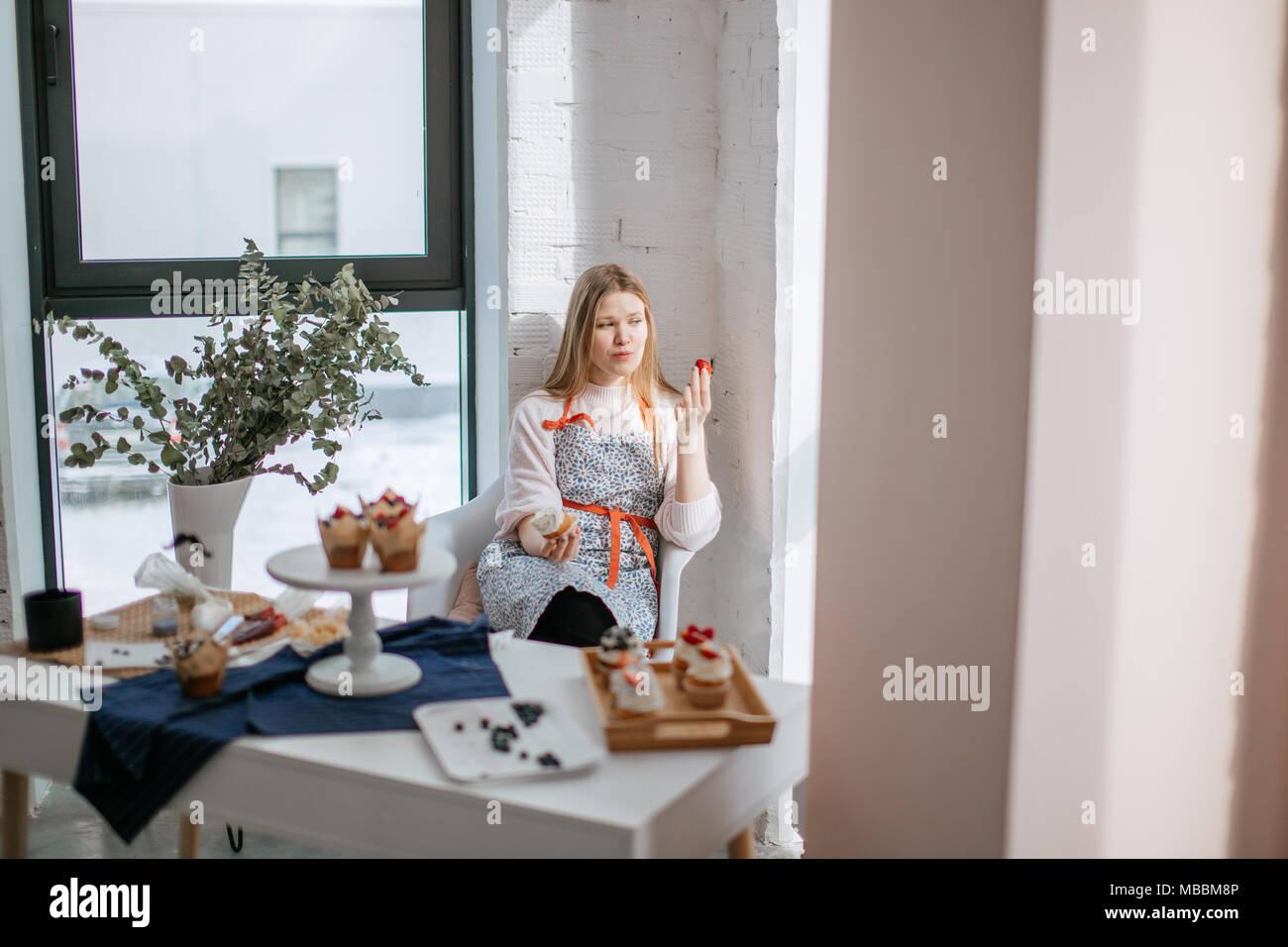Schöne junge Frau essen Cupcake beim Sitzen in der Nähe der Fenster im Cafe Stockbild
