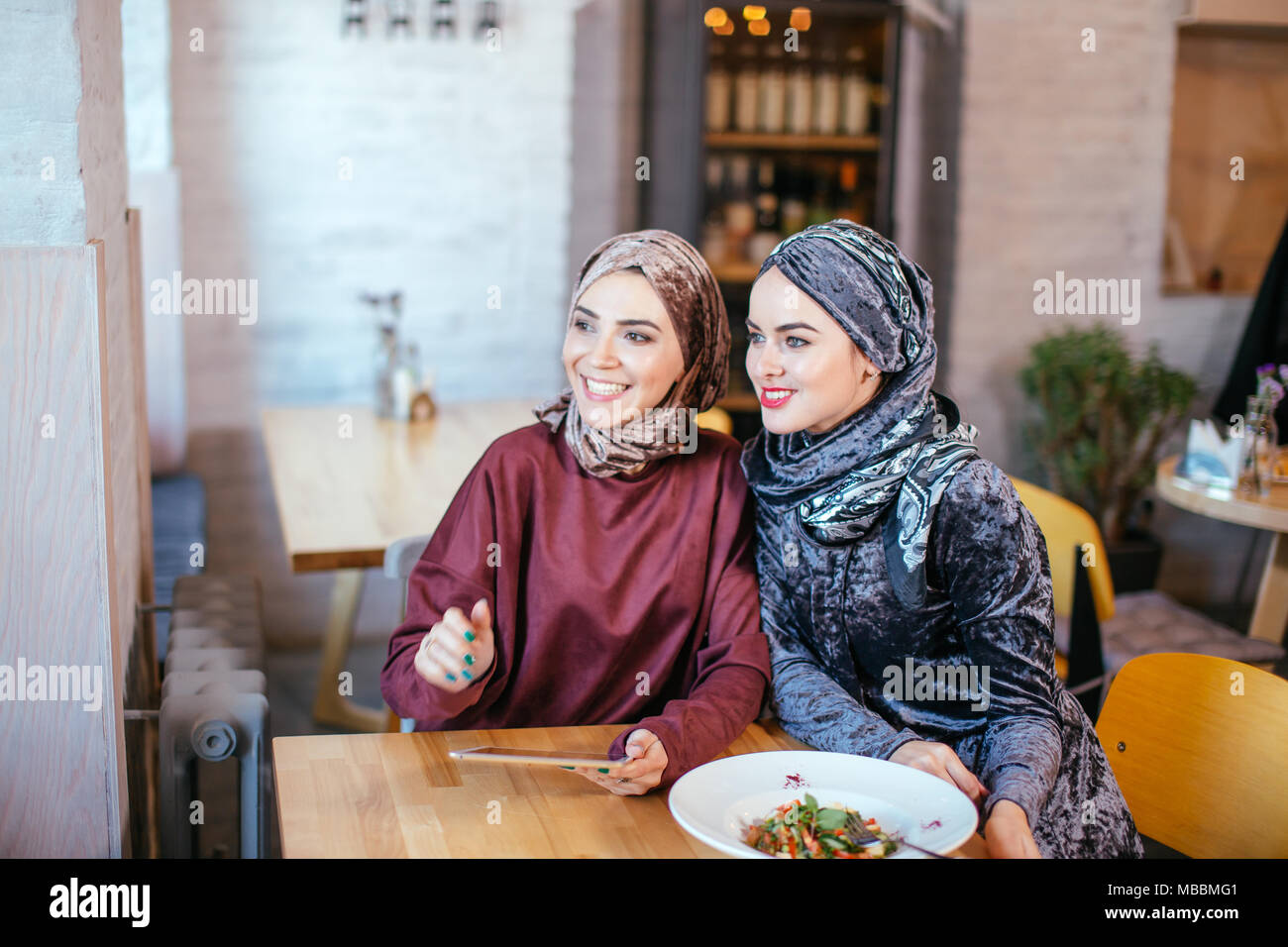 Zwei muslimischen Frauen im Cafe, Shop online über elektronische Tablet Stockbild