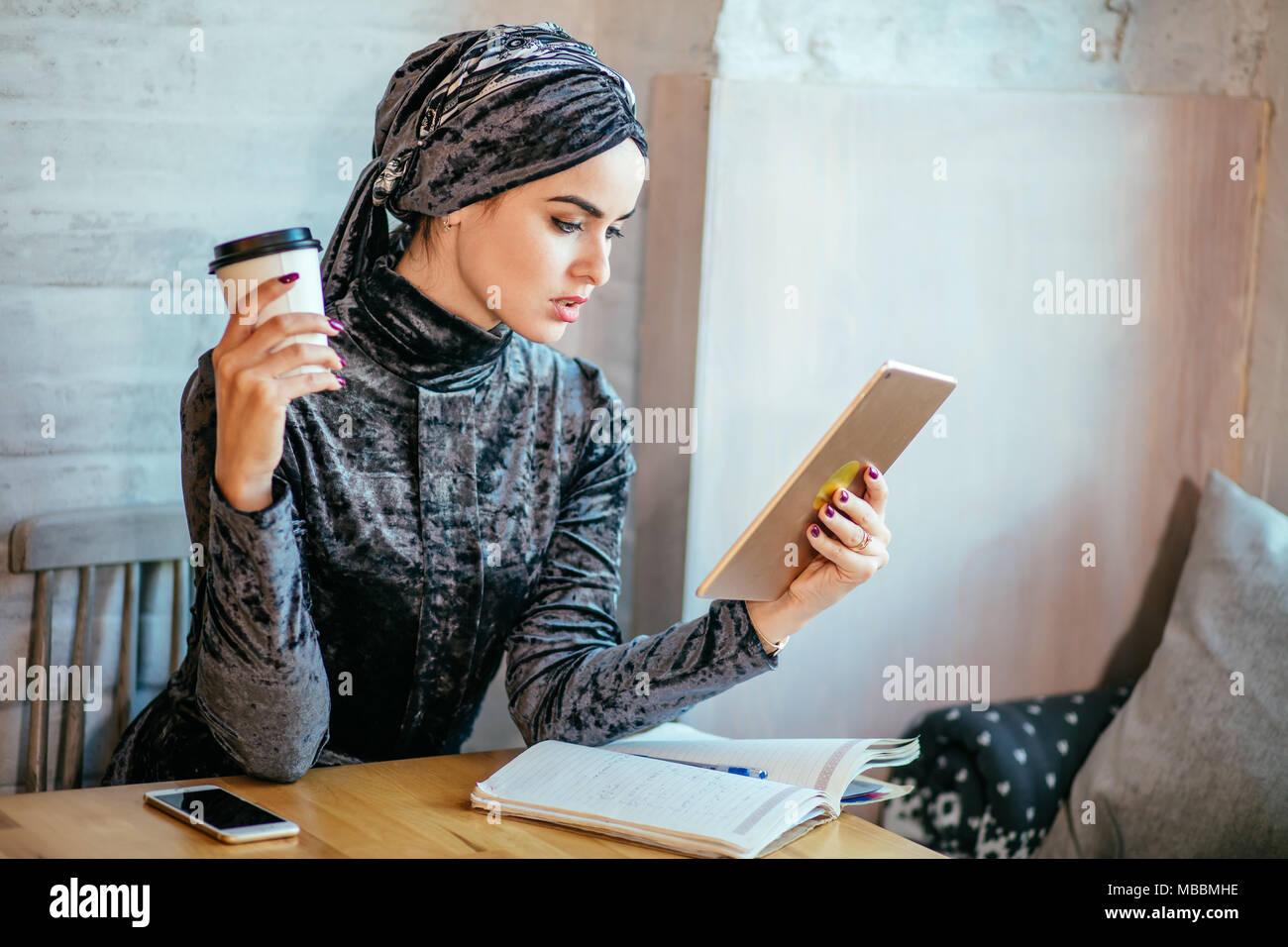 Muslimische Frauen arbeiten mit Tablet- und trinken Kaffee im Cafe Stockbild