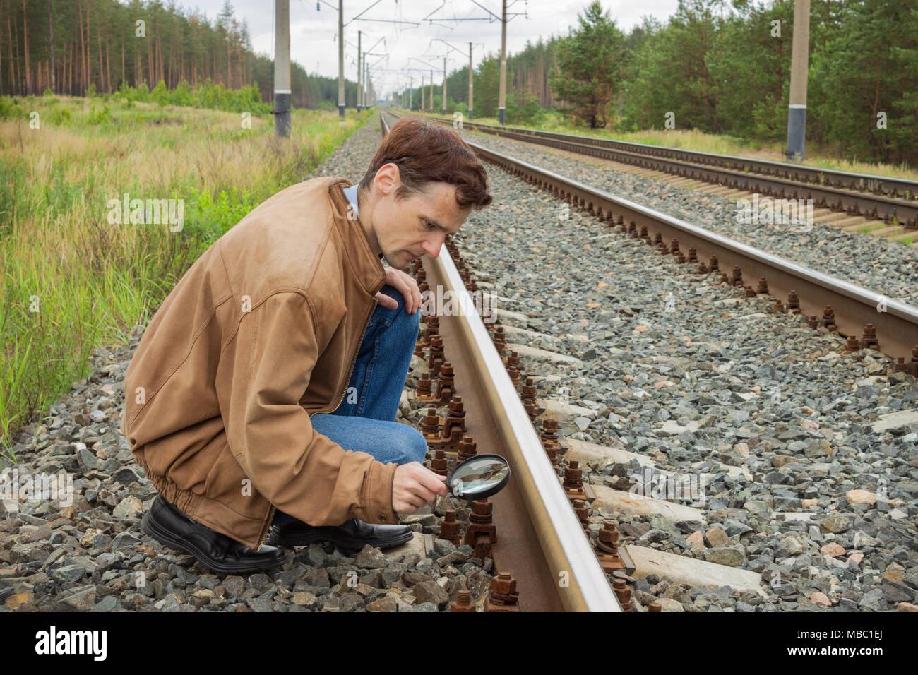 Junger Mann untersucht die Schiene Oberfläche auf der Bahn Stockbild