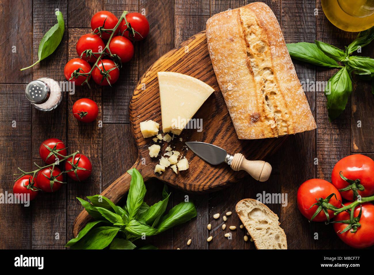 Italienisches Essen Parmesan, Ciabatta Brot, Bruschetta, Tomaten und Basilikum auf rustikalem Holz Hintergrund. Ansicht von oben Stockbild