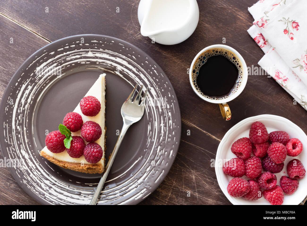 Stück Käsekuchen mit Himbeeren und Tasse Kaffee auf Holz Tisch. Ansicht von oben Stockbild