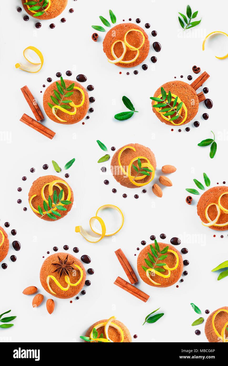 Oatmeal cookie Muster flach. Food Styling Tipps Muster aus Keksen, Schokolade Swooshes und Ringe, Zimt, Zitronenschale und grünen Blättern. Stockbild