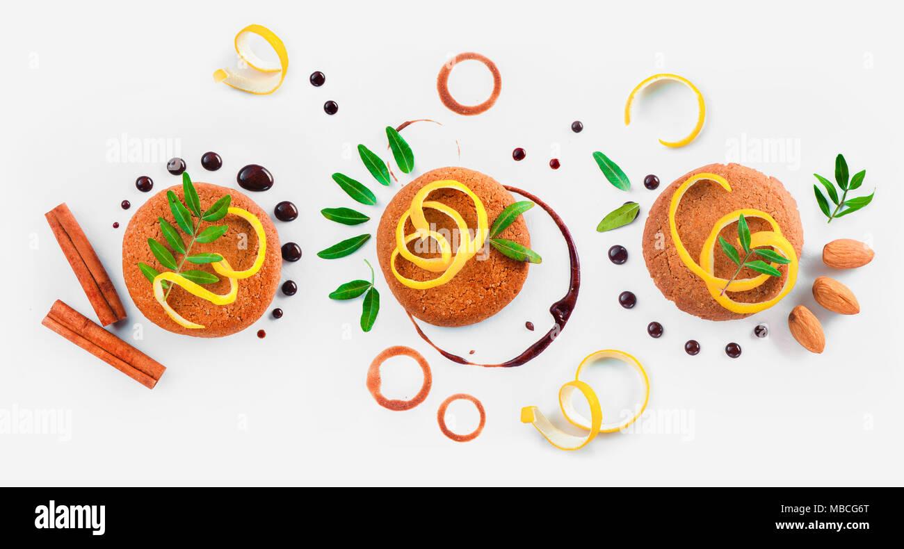 Cookie Dekoration flach. Food Styling Tipps Muster aus Keksen, Schokolade Swooshes und Ringe, Zimt, Zitronenschale und grünen Blättern. Stockbild
