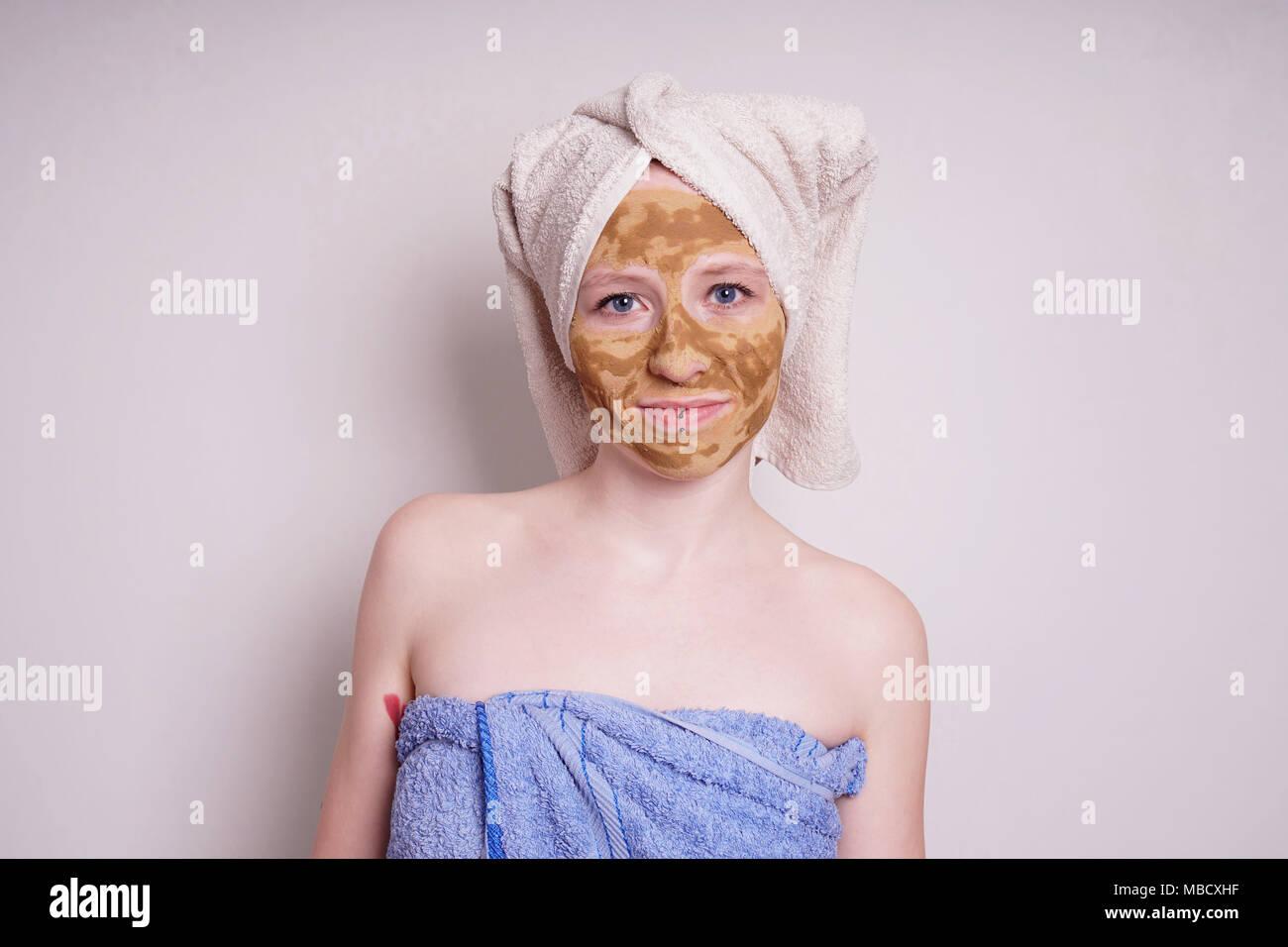 Junge Frau mit der Heilung der Erde oder Lehm beauty Gesichtsmaske in Handtuch gewickelt Stockbild