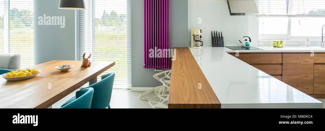 Weiß Arbeitsplatte und violett Heizung in moderne Küche mit Esstisch ...
