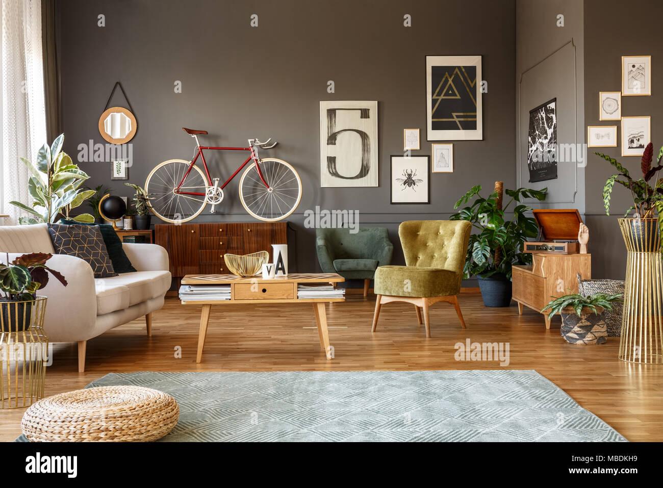 Plakate Auf Die Graue Wand, Vintage Sessel, Weiß , Holz , Tisch Und  Gemustertem Teppich In Einer Kreativen Wohnzimmer Innenraum