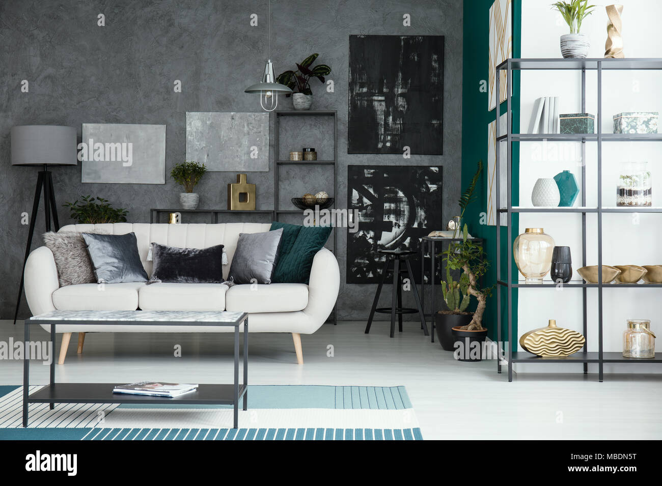 Beige Sofa und Tisch im Wohnzimmer mit Galerie auf graue Wand und ...