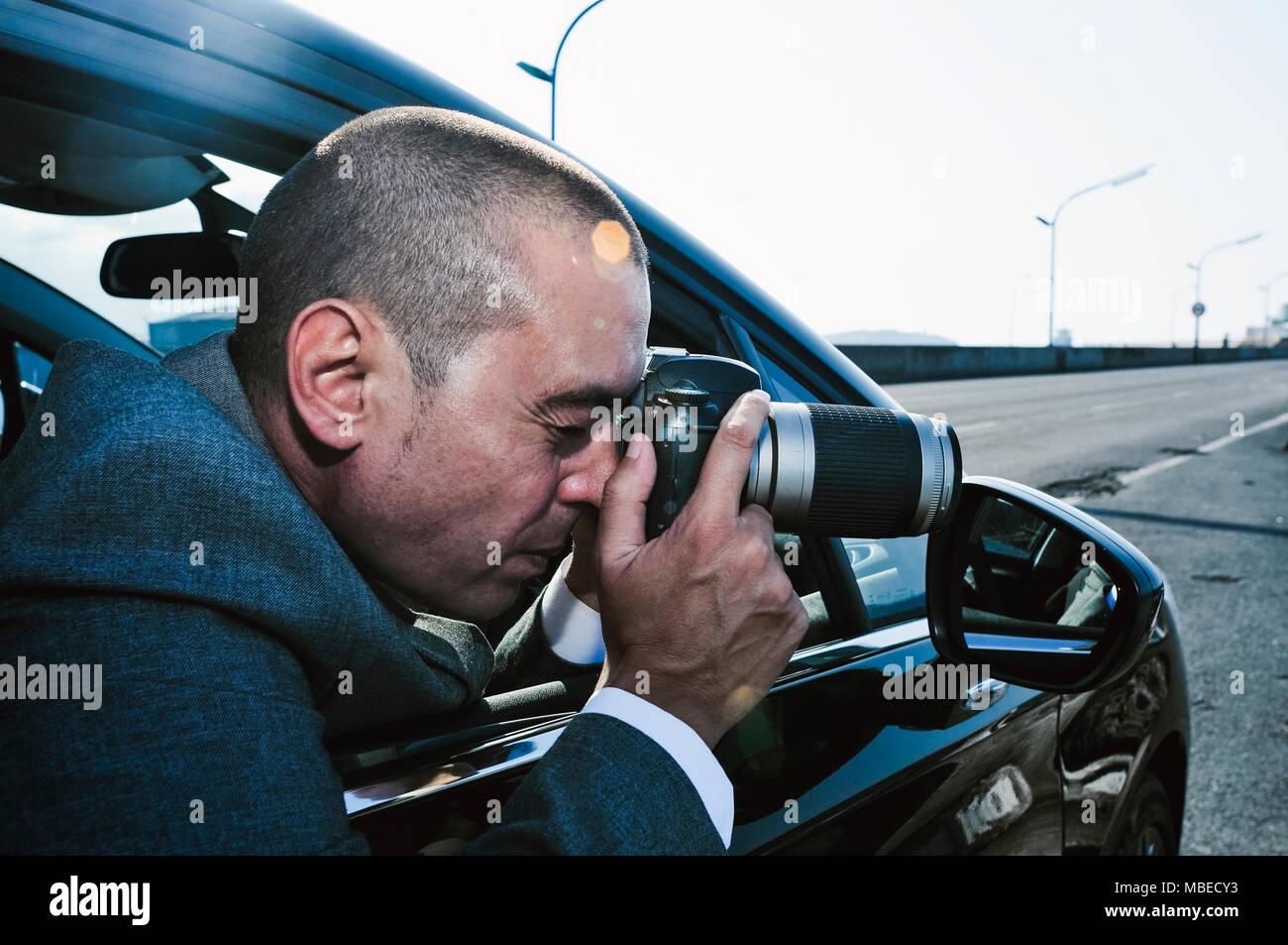 Nahaufnahme eines jungen kaukasischen Detektiv oder Paparazzi Mann, in einem grauen Anzug, Fotos von innen ein Auto Stockbild