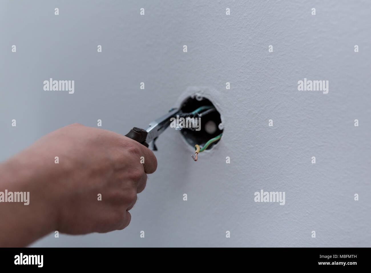 Professionellen Elektriker Abisolieren der Kabel, Schalter und Steckdosen in einem Wohngebiet elektrische Installation verbinden Stockfoto