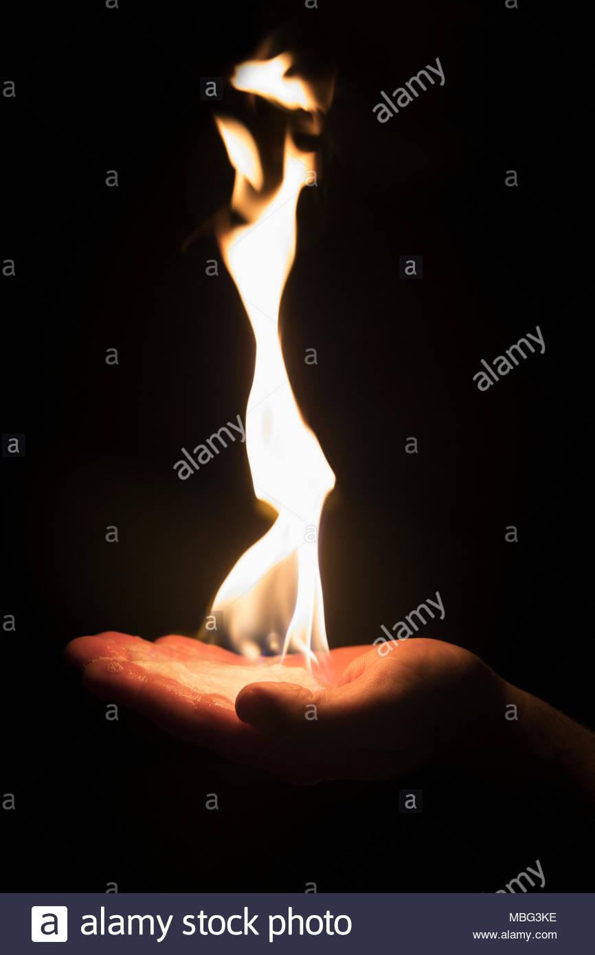 Hand, kreativ, inspirierend Flamme auf schwarzem Hintergrund Stockbild