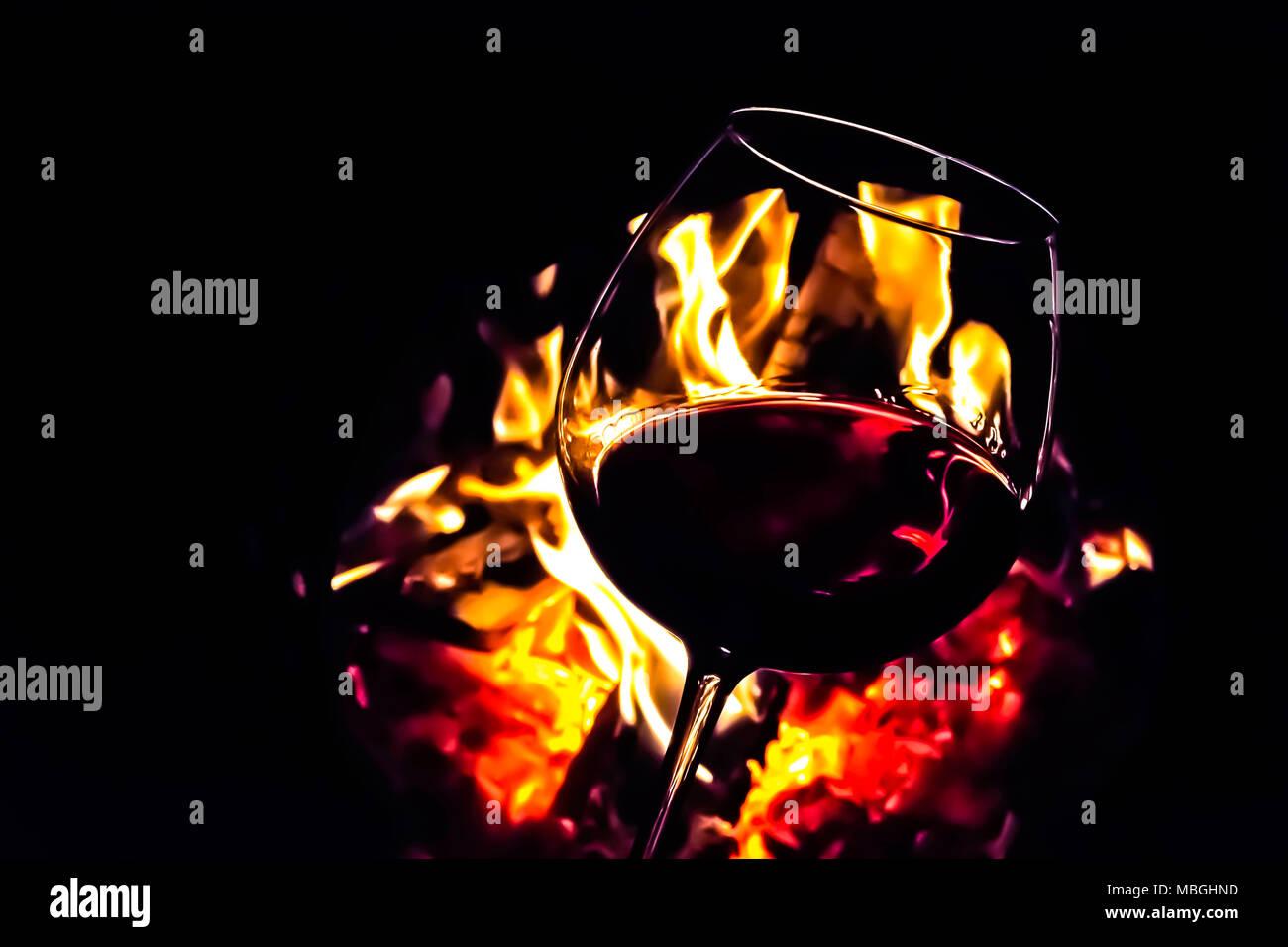 Glas Rotwein beleuchtet durch Lagerfeuer Flammen. Moody dunkle ...