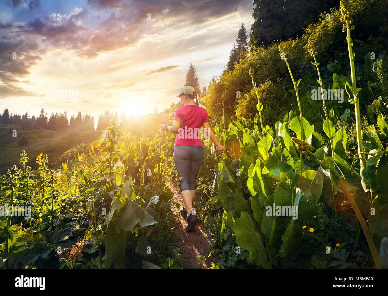 Schöne sportliche Mädchen in rosa Hemd zu Fuß in den Berg Trail bei bewölktem Himmel Sonnenuntergang Stockbild