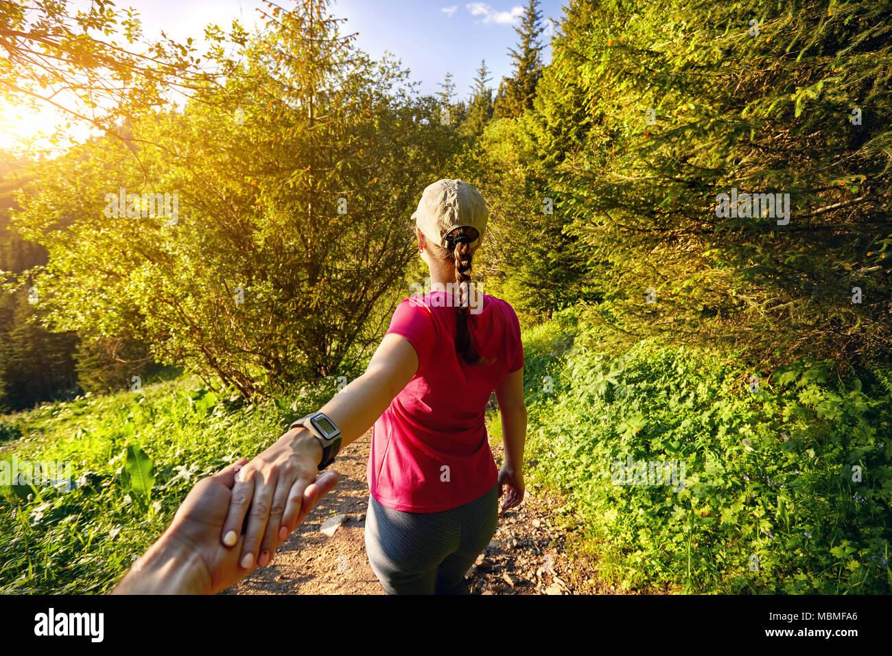 Schöne sportliche Mädchen in rosa Shirt holding Mann von Hand, und was ihn zu dem Berg Trail bei Sonnenuntergang Stockbild
