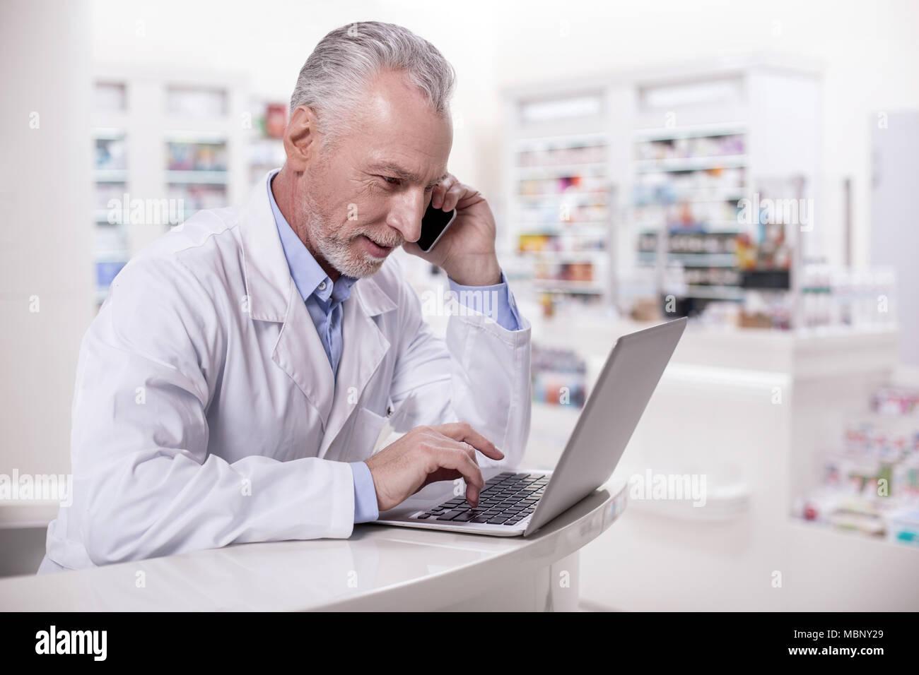 Attraktive männliche Apotheker Beratung mit Arzneimittel-hersteller Stockbild