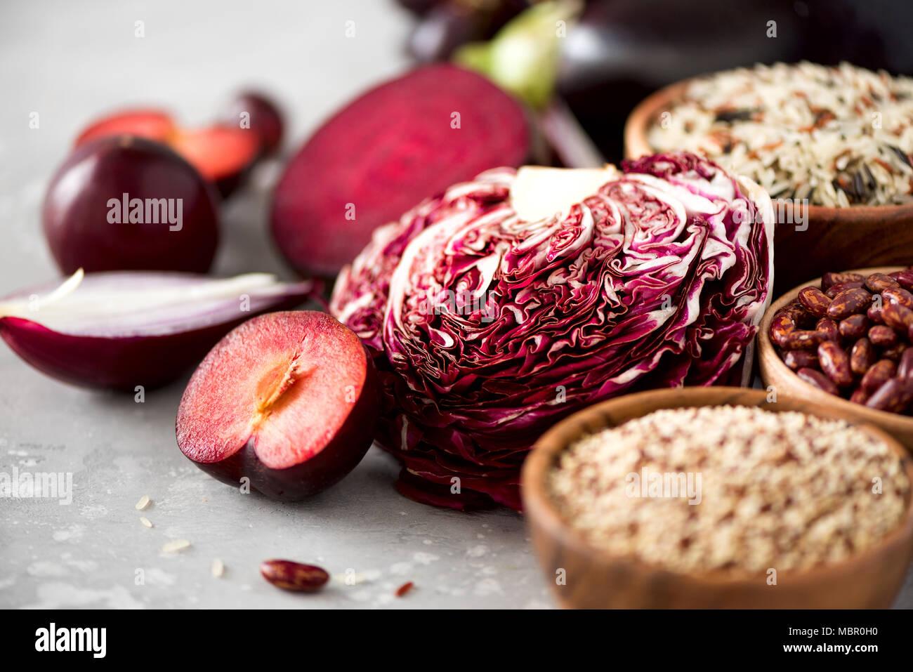 Zutaten zum Kochen, Kopieren, Ansicht von oben, flach. Lila Gemüse, Obst auf grauem Hintergrund. Violett Aubergine, Rüben, Blumenkohl, lila Bohnen, Zwetschgen, Zwiebel, Traube, Quinoa, Reis. Stockbild