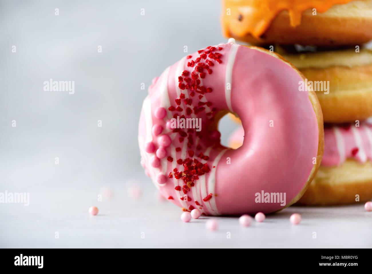 Stapel von Verglasten bunt sortierte Donuts mit Streuseln auf grauem Zement Hintergrund. Kopieren Sie Platz. Süße Krapfen für Kinder Stockbild
