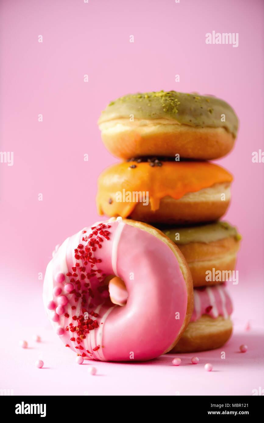 Stapel von Verglasten bunt sortierte Donuts mit Streuseln auf rosa Hintergrund. Kopieren Sie Platz. Süße Krapfen für Kinder Stockbild