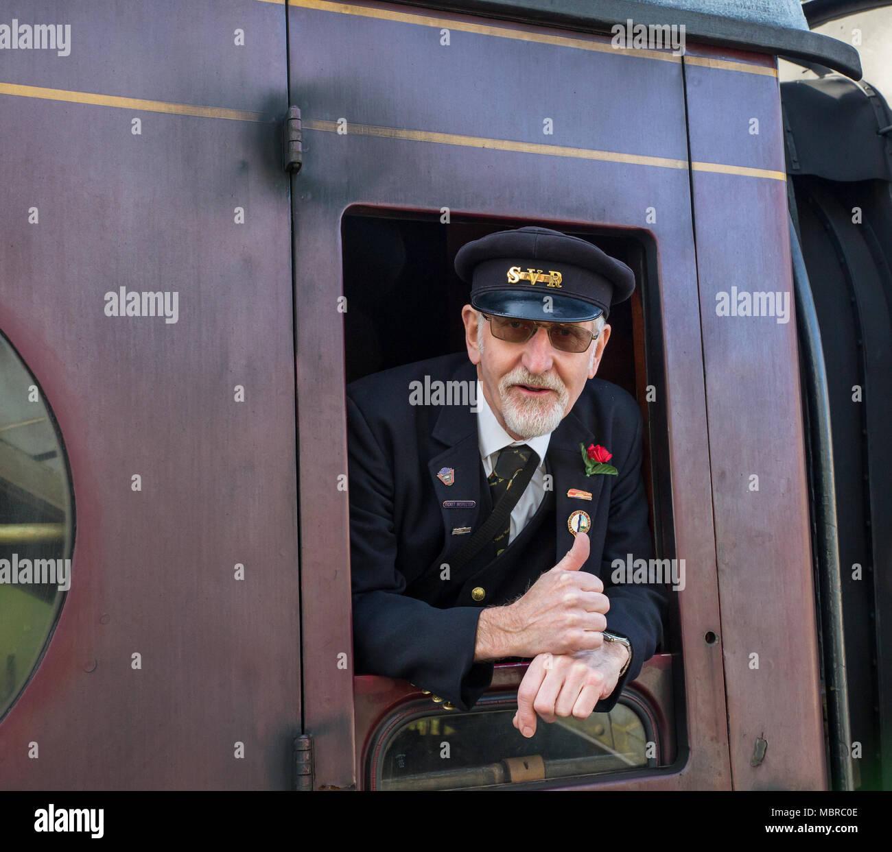 """In der Nähe von Jolly SVR Guard, in offiziellen Kappe, erfasst als er aus dem vorbeifahrenden Wagen geben eine glückliche """"Daumen hoch"""" balanciert Plattform Fotograf lehnt. Stockbild"""