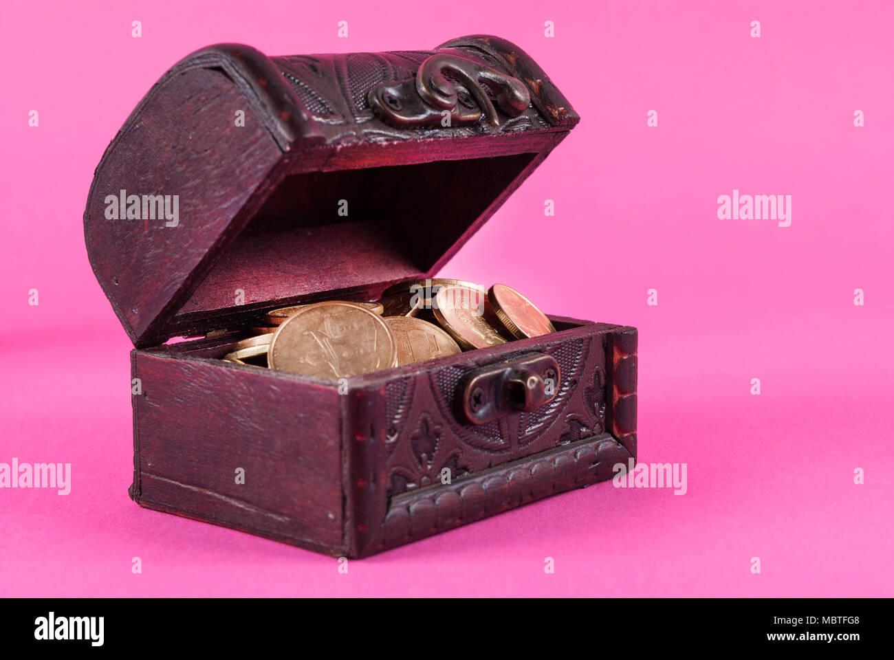 Münzen in einer alten Holzkiste auf einem rosa Hintergrund Stockbild