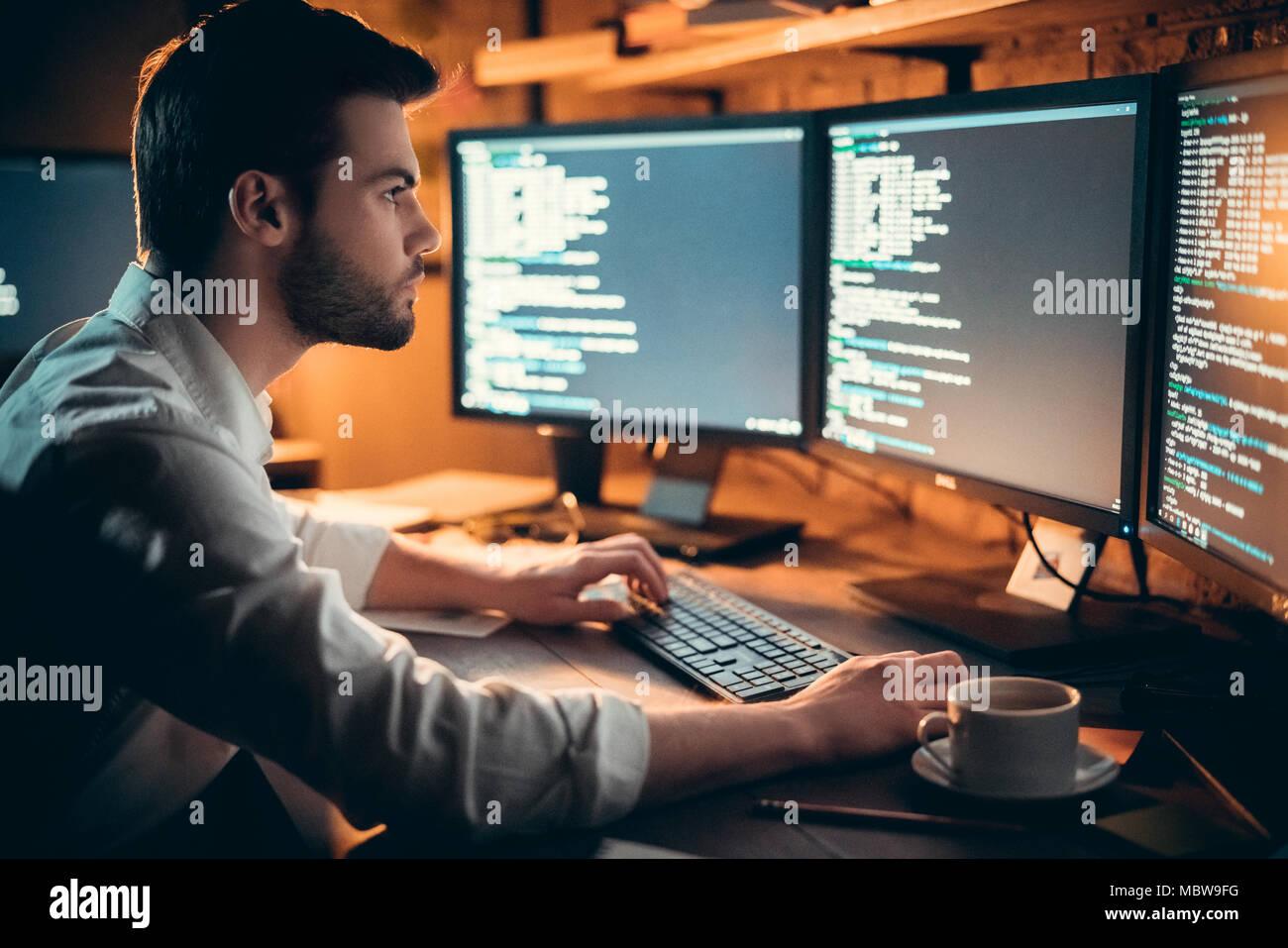 Schwerpunkt junge Entwickler coding spät im Büro schreiben Skript auf dem Computer Monitoren gezeigt, schwere stattlichen coder Programmer hacker Programmierung developi Stockfoto
