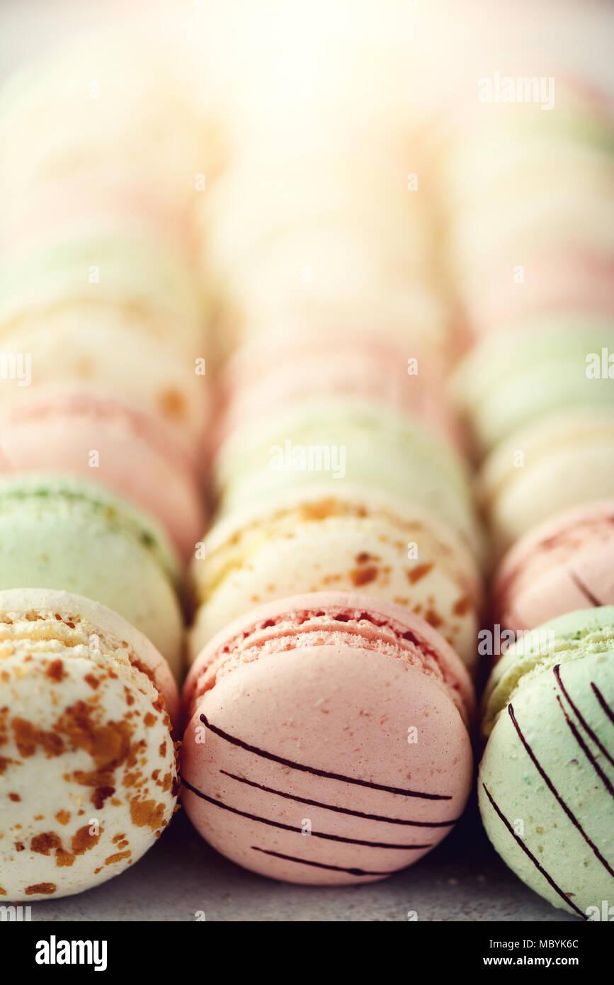 Bunte französische Makronen flach. Pastellfarben Pink, Grün, Gelb macarons mit Kopie Raum, Ansicht von oben. Feiertage und Feste Konzept. Süßes Geschenk für Frau, Mädchen Stockbild