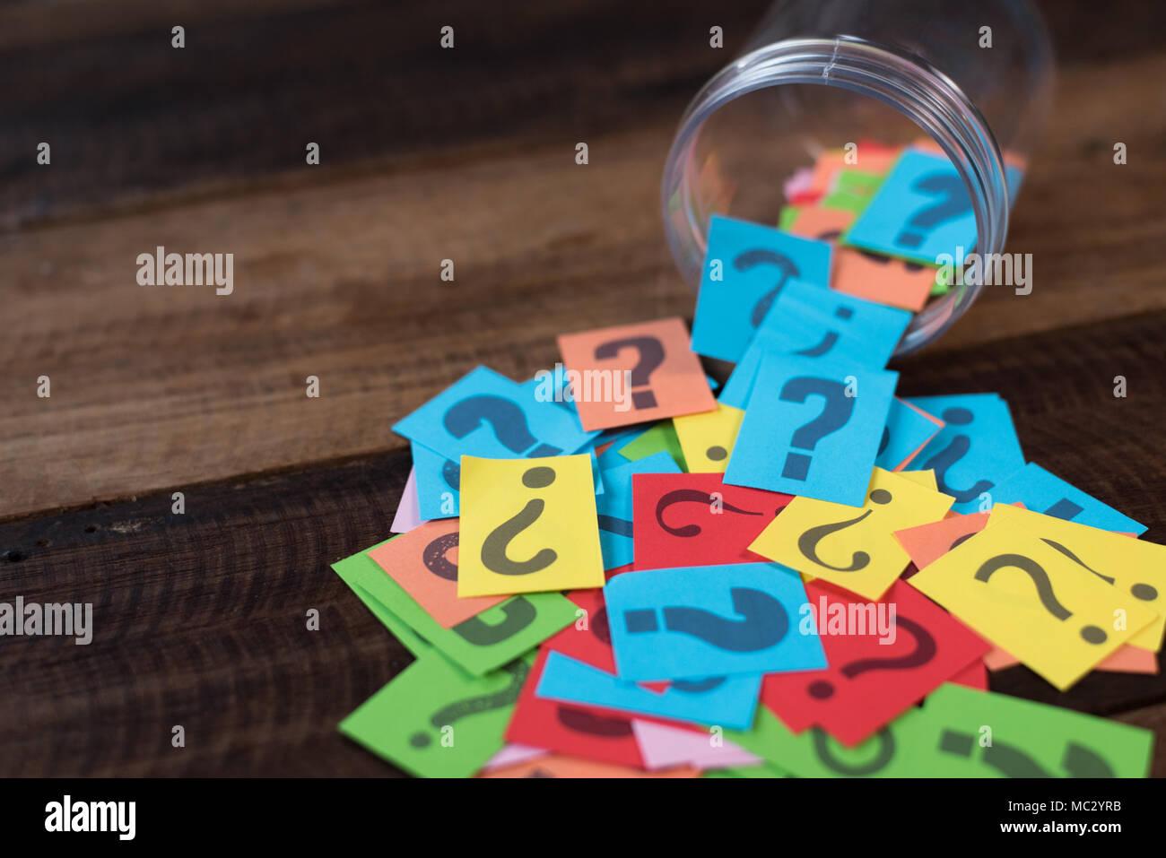 Bunte Papier mit Fragezeichen in einem Kunststoffbehälter auf hölzernen Tisch. Fragen und Diversity Konzept. FAQ und Q&A Hintergrund Konzept Stockfoto