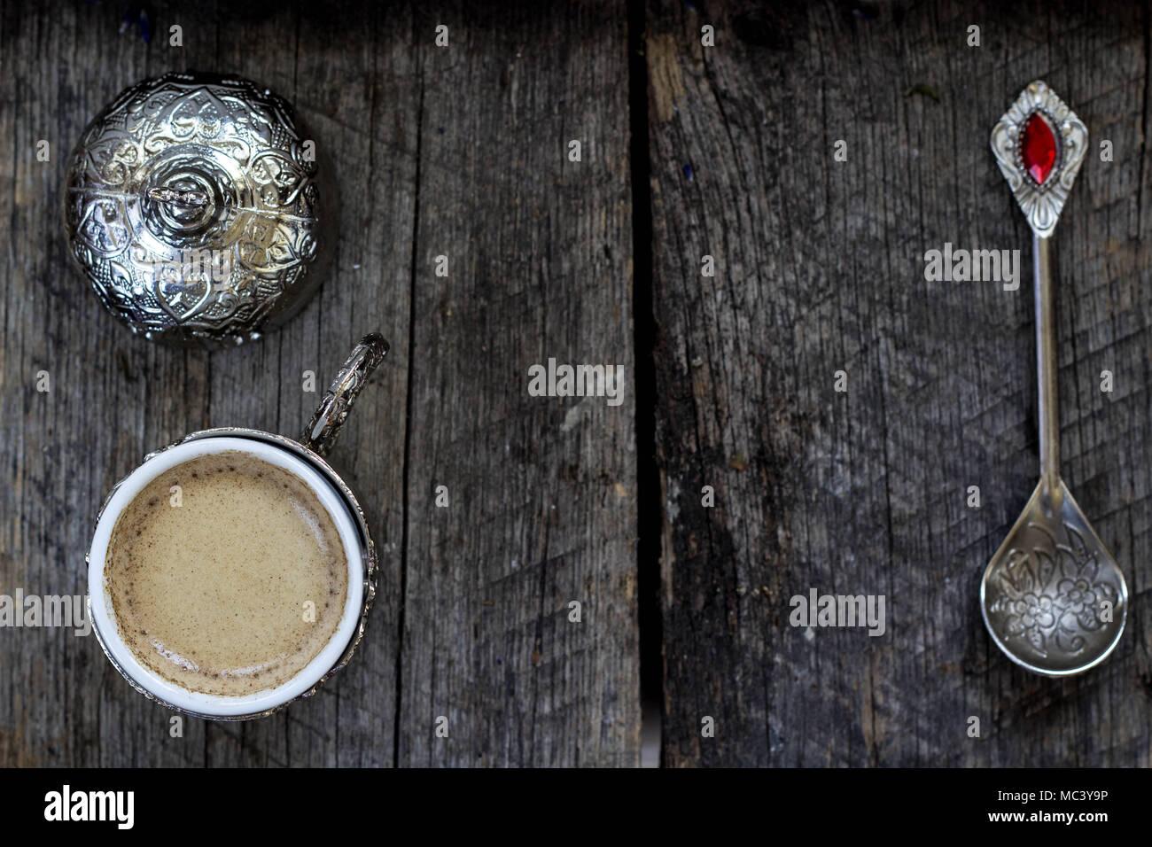 Türkischer Kaffee in einer traditionellen Tasse und Teelöffel auf einer hölzernen Hintergrund Stockbild