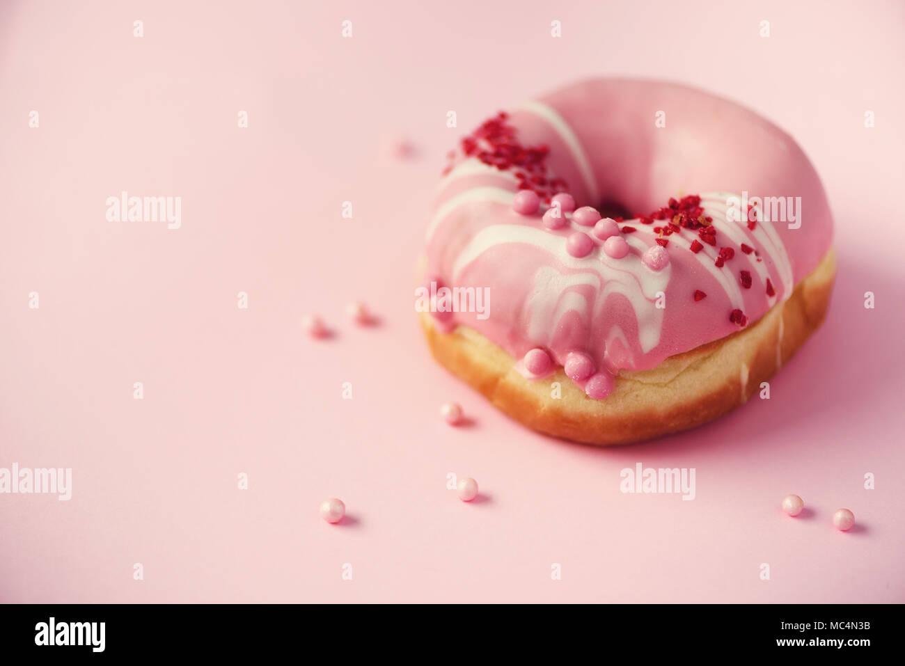Süße Krapfen mit rosa Zuckerglasur auf hellen Hintergrund. Leckere Krapfen auf rosa Textur, Kopieren, Ansicht von oben Stockfoto