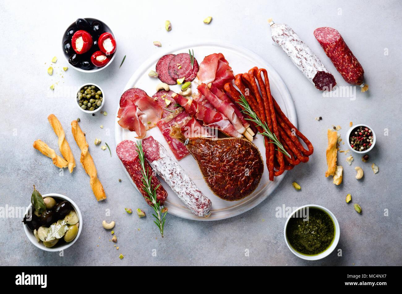 Traditionelle italienische Antipasti, Schneidbrett mit Salami, kalt geräucherte Fleisch, Schinken, Schinken, Käse, Oliven, Kapern auf grauem Hintergrund. Fleisch und Käse Vorspeise. Top Anzeigen, Kopieren, flach Stockbild