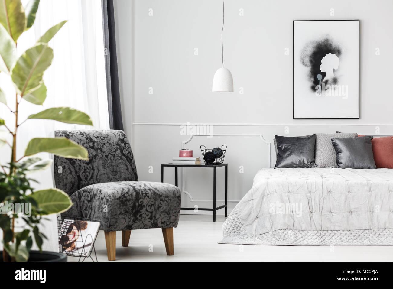 Grau Sessel Stand In Hellen Weiblichen Schlafzimmer Innenraum Mit Poster An  Der Wand Und Silber Kissen Auf Dem Bett
