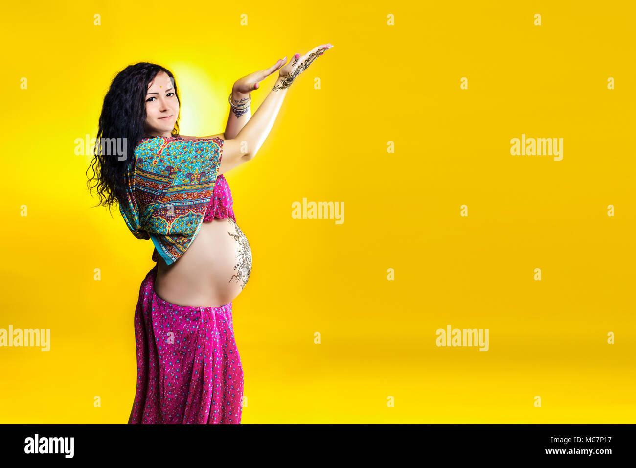 Schwangere Frau in der indischen Sari mit mehendi Henna Tattoo auf dem Bauch gemalt, Spaß Aprilscherze auf gelbem Hintergrund. Stockfoto