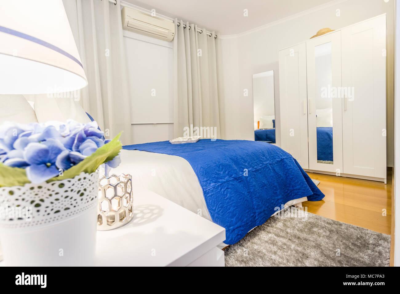 Ein elegantes Schlafzimmer in Weiß und Blau mit schalten Sie Lichter ...