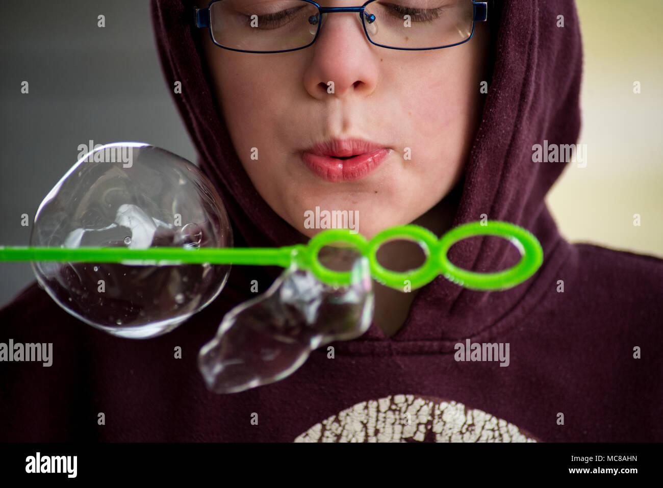 Ein Junge bläst Seifenblasen in die Kamera. Stockbild