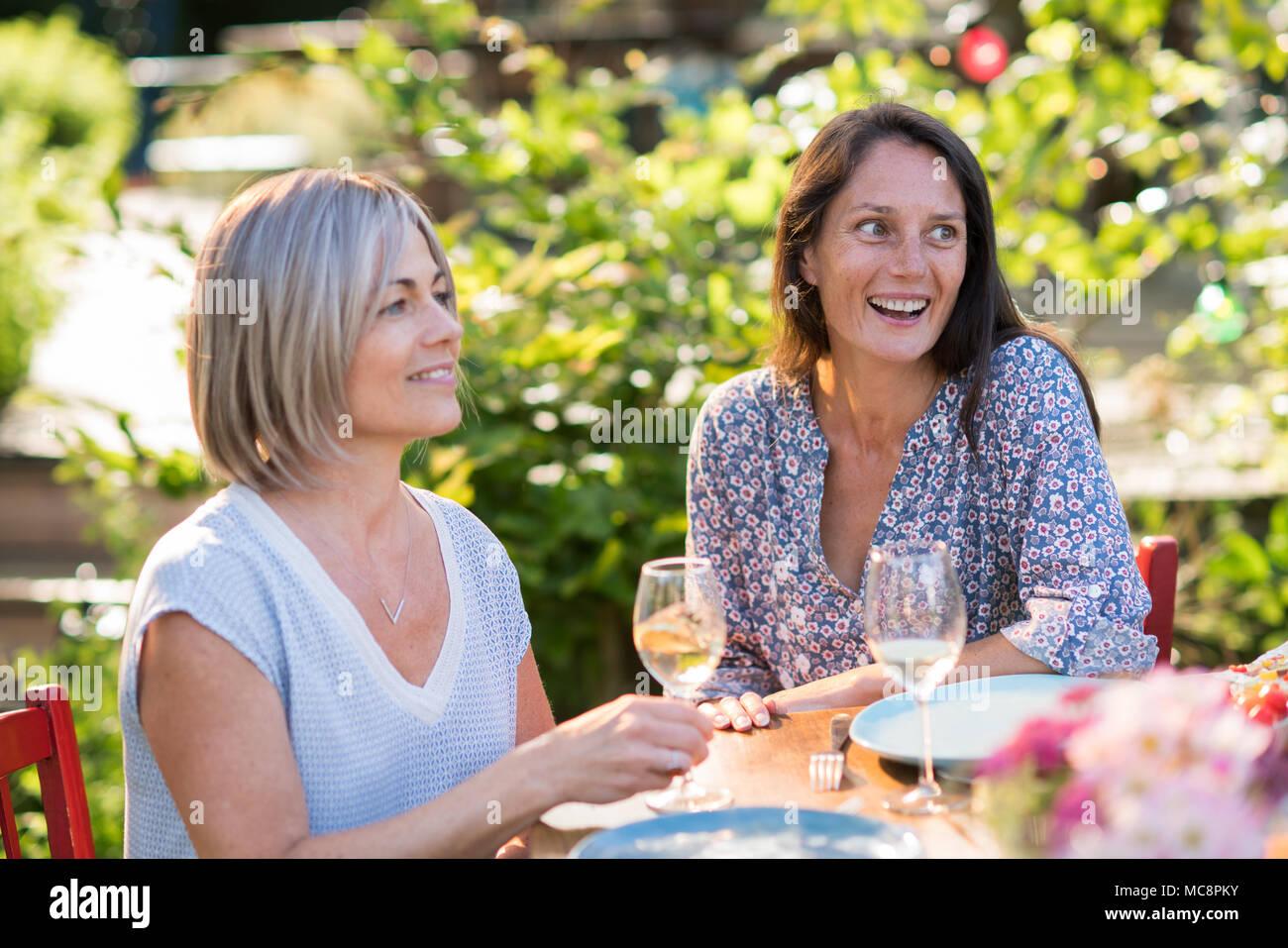 Portrait von zwei schönen Frauen in den Vierzigern, eine Brünette und eine Blondine. Sie teilen sich eine Terrasse im Garten mit Freunden Stockbild
