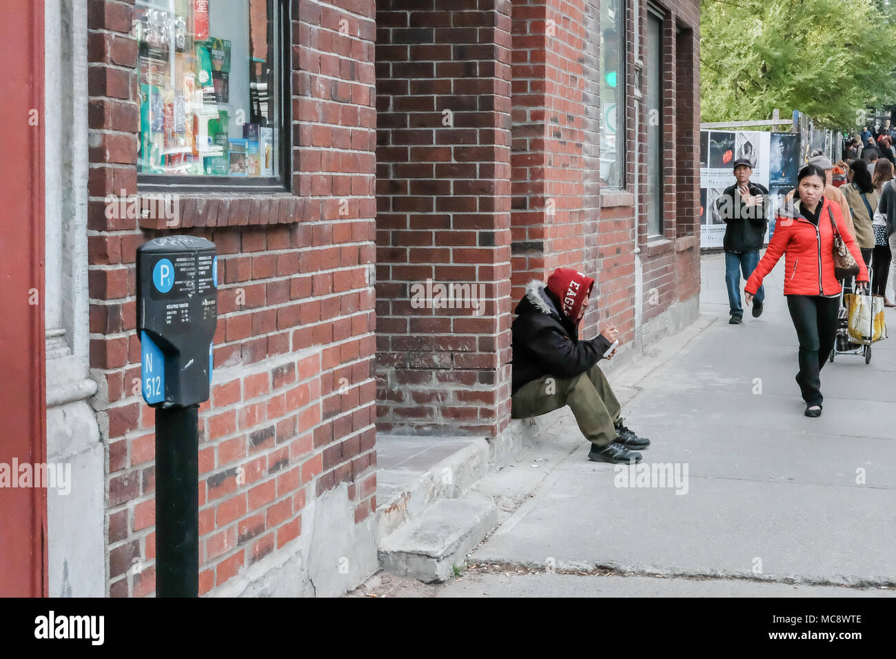 Obdachlose erwachsene Männchen gesehen, für Nächstenliebe, während innerhalb einer Tür in einer geschäftigen Nordamerika Straße sitzen, während Menschen, die auf dem Bürgersteig. Stockbild
