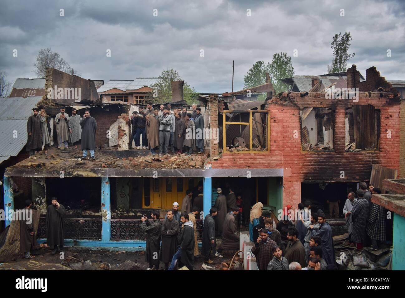 Einheimische versammeln sich in der Nähe der Trümmer von Häusern, die in einem Gunbattle zwischen Kräften und pro-freiheit Rebellen in Khudwani im Süden von Kaschmir Bezirk Kulgam am 11. April 2018 zerstört wurden. Vier Zivilisten und 1 Armee Mann wurden getötet und über 150 Zivilisten wurden bei Auseinandersetzungen verletzt 3 Rebellen durch die Vorteile der riesigen Menge nahe Begegnung Ort konfektioniert entkommen Stockbild