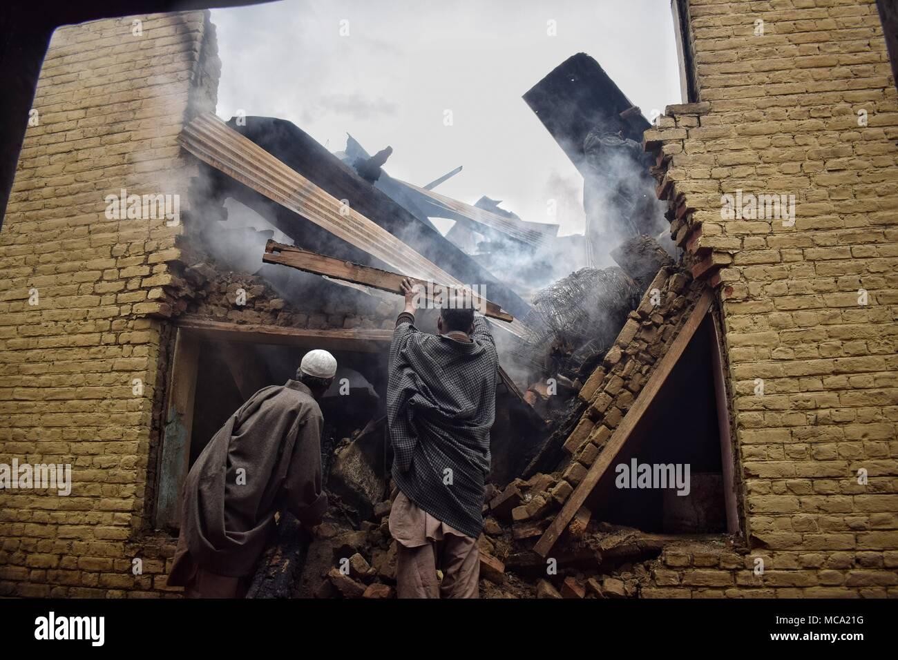 Einheimische clearing brennenden Sachen von Häusern, die von indischen Truppen in einem Khudwani Gunbattle im Bereich des South Kaschmir Bezirk Kulgam am 11. April 2018 zerstört wurden. Vier Zivilisten und 1 Armee Mann wurden getötet und über 150 Zivilisten wurden bei Auseinandersetzungen während der Begegnung verletzt Stockbild