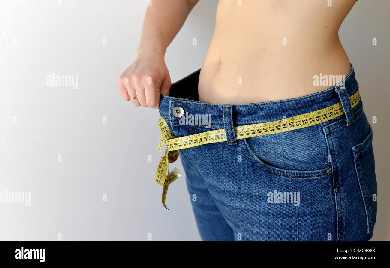 Gewicht-verlust-Konzept. Frau zeigt Ihr Gewicht Verlust durch das Tragen einer alten Jeans. Gesunder Lebensstil, Diät Konzept mit übergroßen Jeans. Stockbild