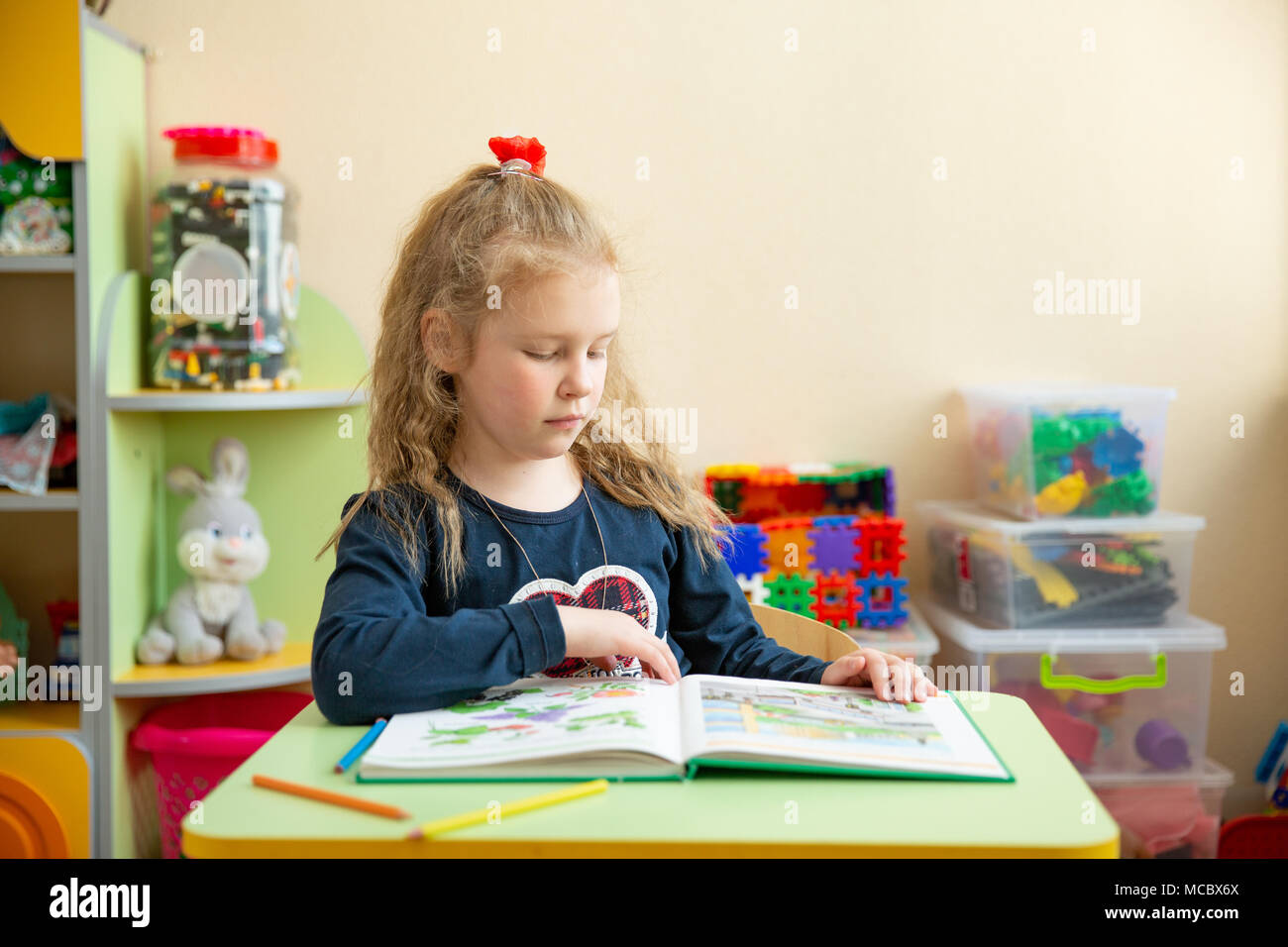 Süße kleine Mädchen Hausaufgaben machen, ein Buch lesen, Malvorlagen ...