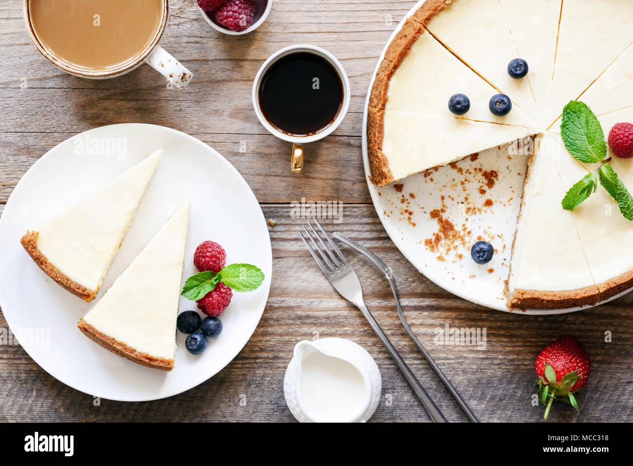 Hausgemachte klassische New York Käsekuchen und Kaffee auf Holztisch. Ansicht von oben Stockbild