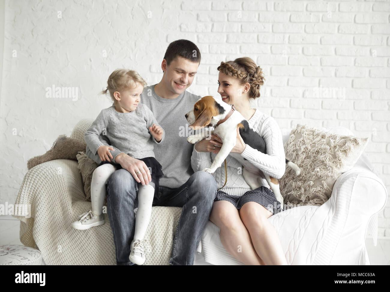 Eltern mit einer kleinen Tochter und pet das Sitzen auf der Couch. Stockfoto