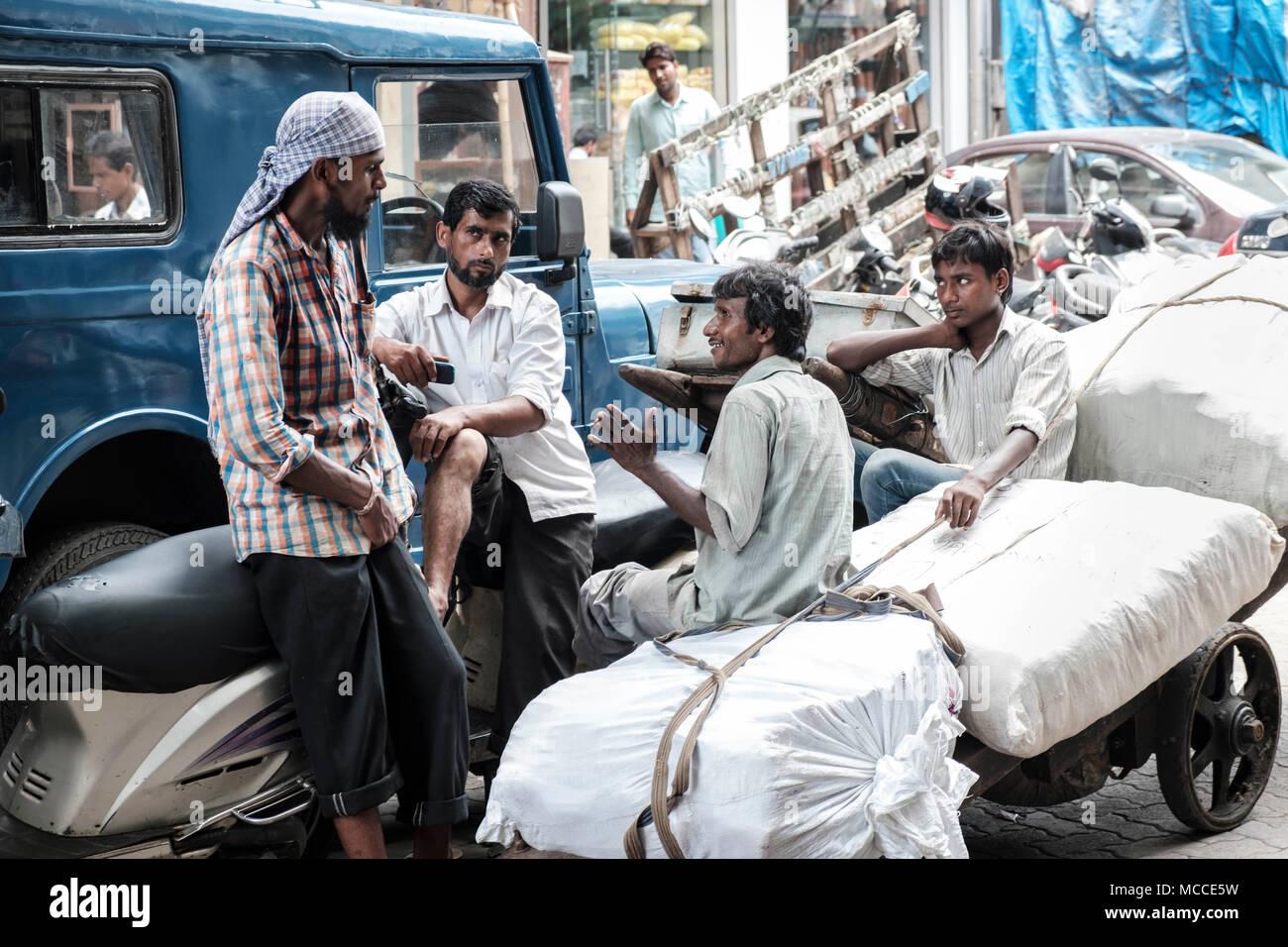 Händler sprechen zusammen auf einer Arbeitspause, Nagdevi Straße in der Nähe von Crawford Market, Mumbai Stockbild