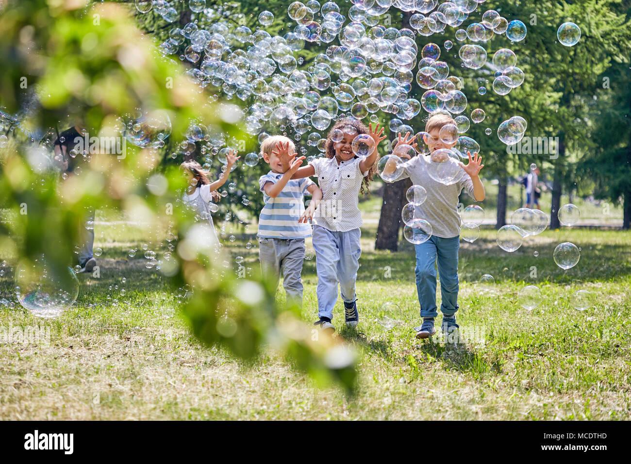 Fröhliche Kinder spielen mit Seifenblasen Stockfoto