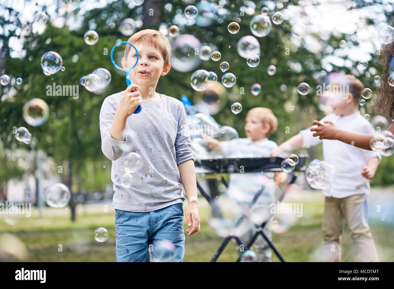 Kleine Jungen machen Seifenblasen Stockbild