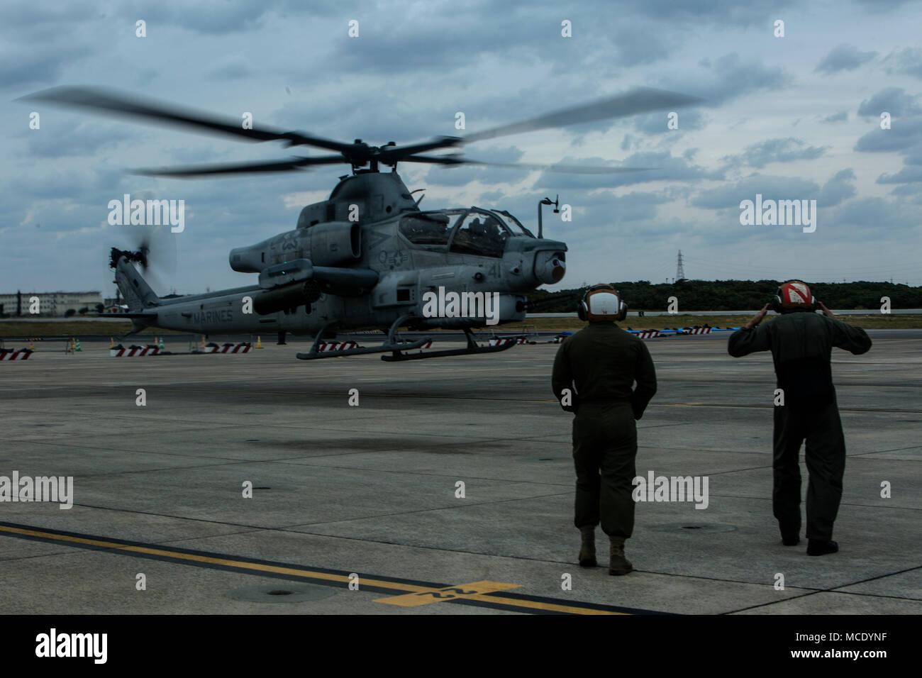 Kapitän Justin S. Morrison und Kapitän Kyle T. Myer Abheben in eine AH-1Z Viper während Sgt. Austin B. Shepard und Lance Cpl. Jesus Gallegos Boden führen Sie während einer Veranstaltung auf der Marine Corps Air Station Futenma, Okinawa, Japan, 8. Februar, 2018. Die Piloten erhalten Flight Training beim Tragen der Gemeinsamen schützende Aircrew Ensemble (JPACE) und Atemschutz Ausrüstung. Die Schulungsveranstaltung wurde Piloten mit dem JPACE vertraut zu machen. Die JPACE wird den Schutz erhöhen über vorhandene Kleider beim verringern Wärmebelastung und Gewicht. Die Geräte bieten Schutz vor Chemikalien Aga Stockbild