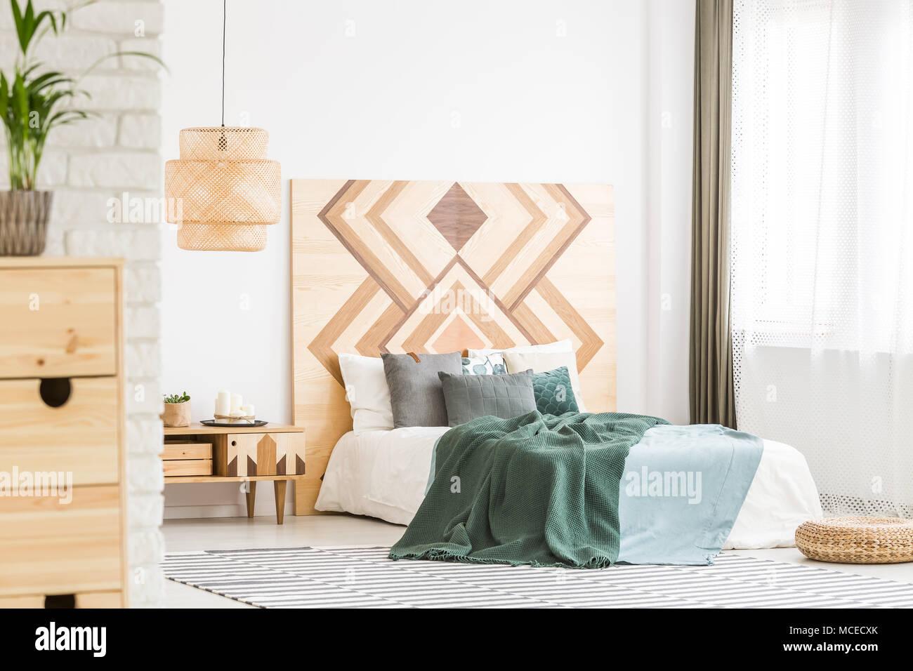 Grün Bettwäsche auf Bett gegen Holz- geometrischen Board in ...