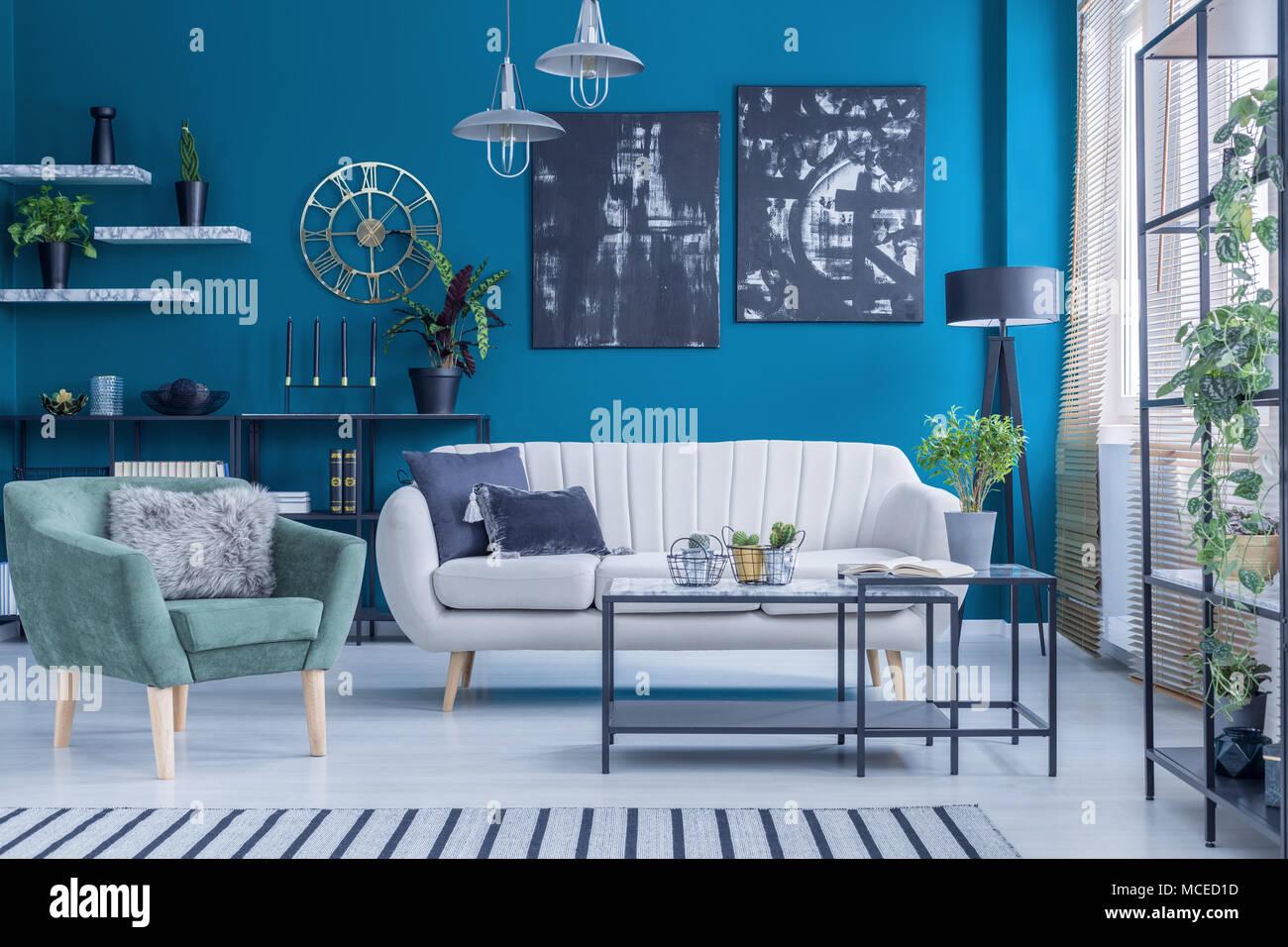 Grün Beige Sofa und Sessel gegen blaue Wand mit schwarzen Gemälde im ...